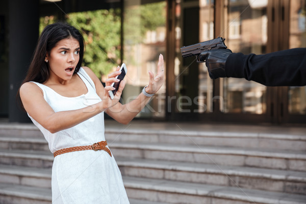 Shocked young woman being threatened by man thief with gun Stock photo © deandrobot