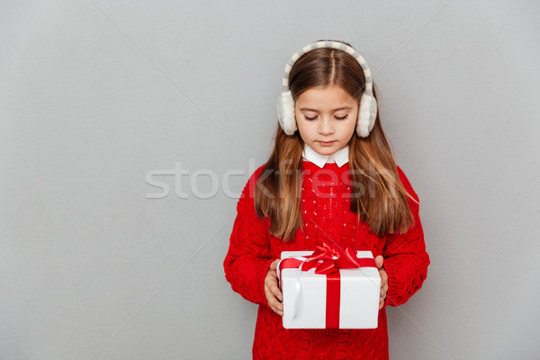 Little girl in red sweater and earmuffs holding present box Stock photo © deandrobot
