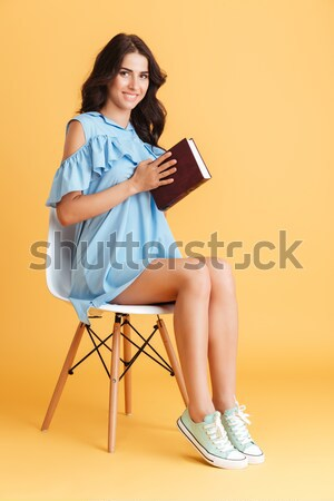 Woman sitting on chair and showing blank screen laptop Stock photo © deandrobot