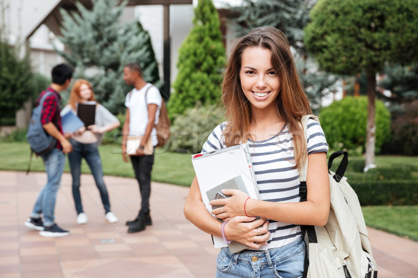 Cheerful woman student with backpack standing in campus Stock photo © deandrobot