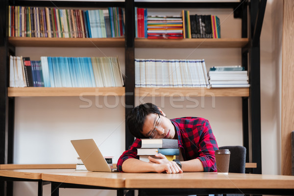 Young man sleeping on books at the library near laptop Stock photo © deandrobot