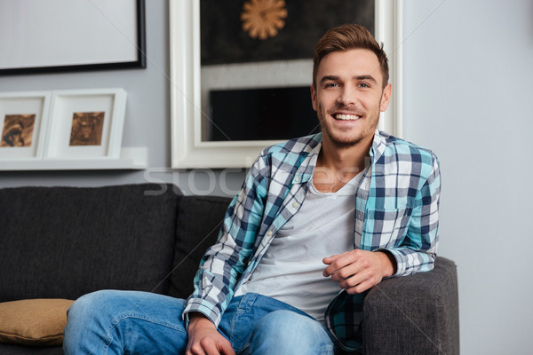 Happy young man sitting on sofa in home Stock photo © deandrobot
