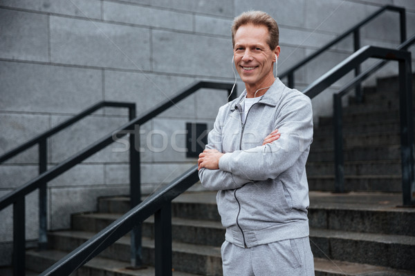Runner standing on stairs with arms crossed Stock photo © deandrobot