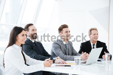 Side view of Smiling Business people by the table Stock photo © deandrobot