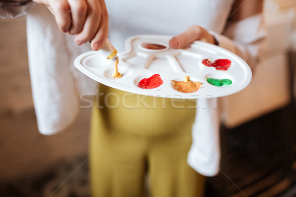 Cropped photo of hand holding palette with paints Stock photo © deandrobot