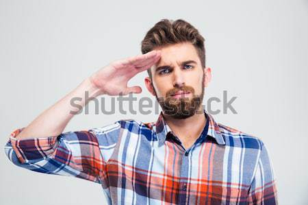 Surprised bearded man in plaid shirt holding torn banknote Stock photo © deandrobot