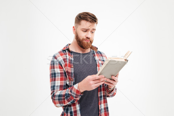 Handsome bearded young man in checkered shirt reading book Stock photo © deandrobot