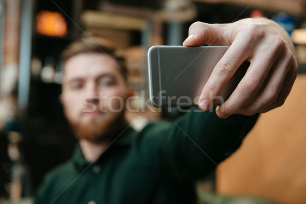 Young man sitting at barbershop and take a selfie Stock photo © deandrobot