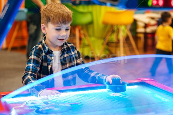 Cute little boy playing air hockey at indoor amusement park Stock photo © deandrobot