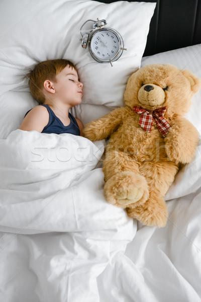 Cute boy sleeping with teddy bear in bed near alarm. Stock photo © deandrobot