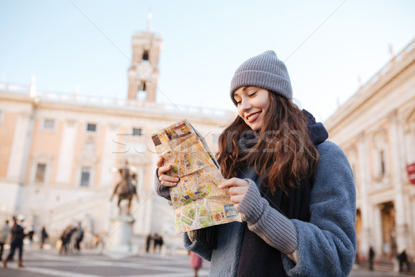 Happy woman standing and using map in old city Stock photo © deandrobot