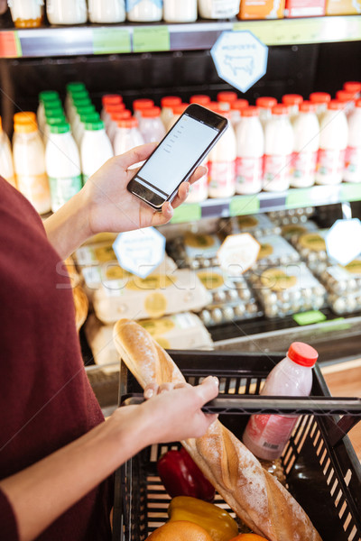 Stock photo: Woman doing shopping and using mobile phone in grocery shop