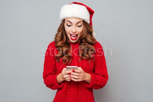 Meglepett fiatal nő mikulás kalap mobiltelefon vonzó Stock fotó © deandrobot