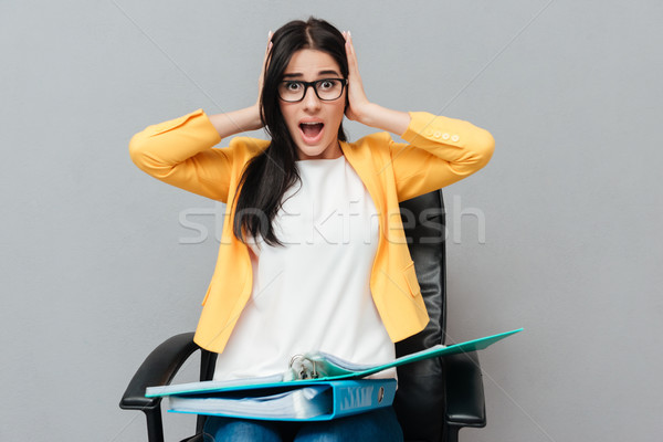 Confundirse mujer carpetas sesión mirando Foto stock © deandrobot