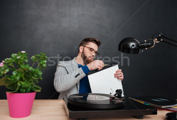 Focused bearded young businessman using turntable and vinyl record Stock photo © deandrobot