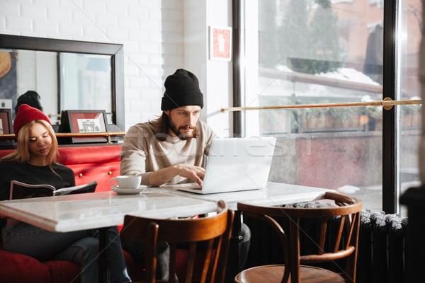 Homme utilisant un ordinateur portable petite amie lecture Journal café Photo stock © deandrobot