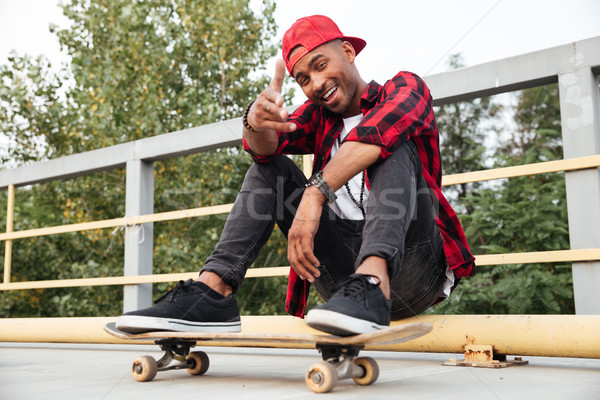 Cheerful man sitting with skateboard and pointing finger at camera Stock photo © deandrobot