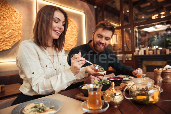 Young loving couple sitting in cafe and eating. Stock photo © deandrobot