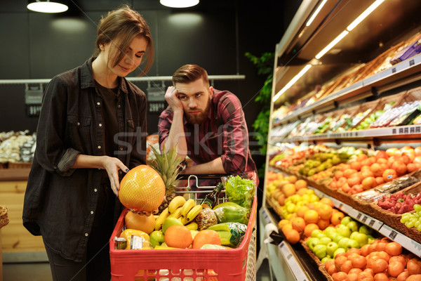 Loving couple in supermarket with shopping trolley Stock photo © deandrobot