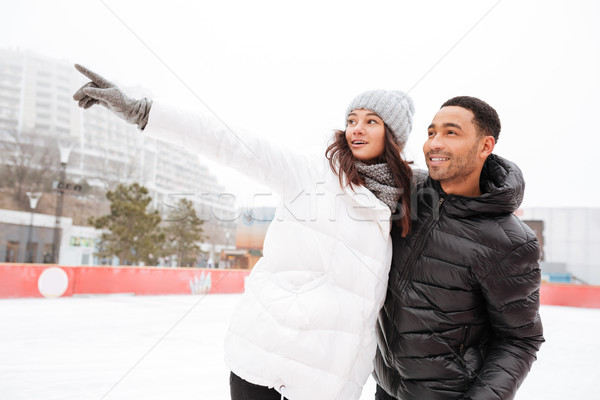 Happy loving couple skating at ice rink outdoors. Stock photo © deandrobot