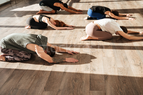 Group of people relaxing and practicing yoga Stock photo © deandrobot