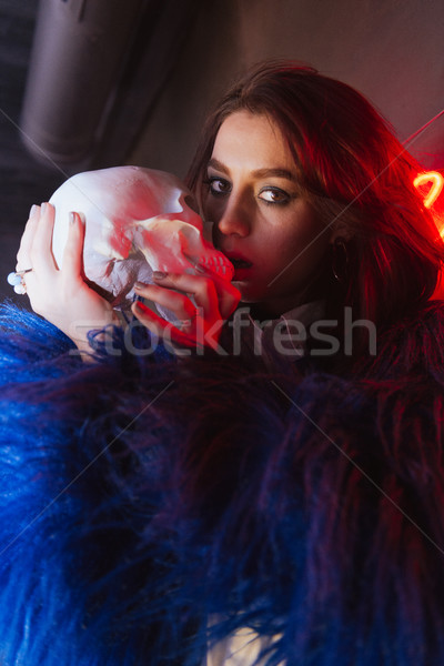Amazing young lady holding at artificial skull. Stock photo © deandrobot