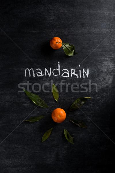 Mandarines over dark chalkboard background Stock photo © deandrobot