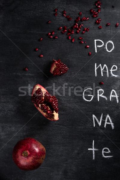 Pomegranate over dark chalkboard background Stock photo © deandrobot