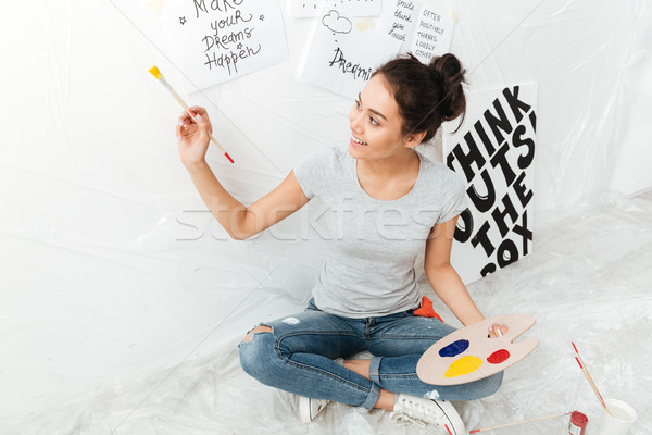 Happy young lady artist sitting on floor over white background. Stock photo © deandrobot