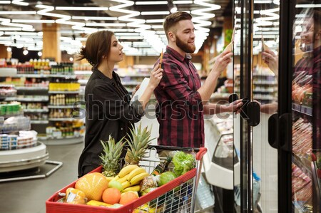 Happy cashier woman on workspace in supermarket shop Stock photo © deandrobot