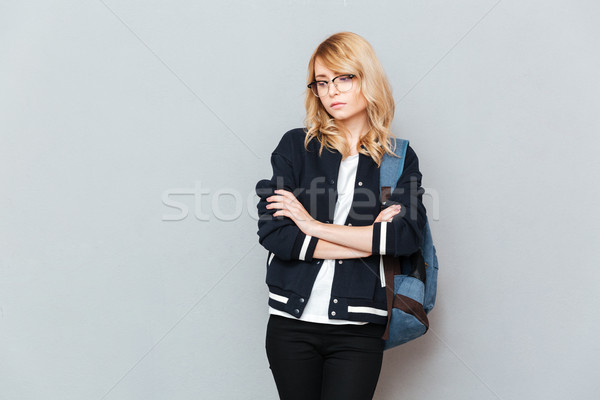 Sad young lady student wearing glasses with backpack Stock photo © deandrobot