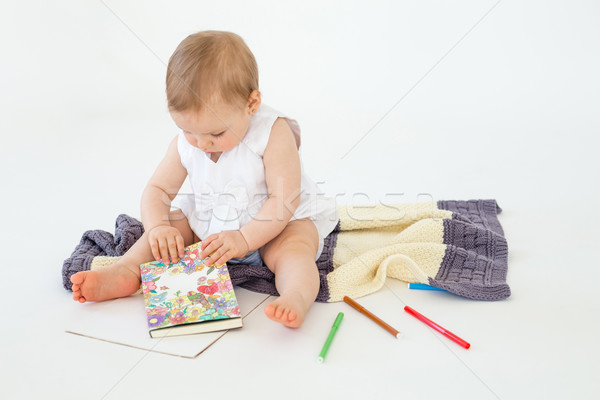 Stock photo: Baby girl sitting on floor near markers and colouring