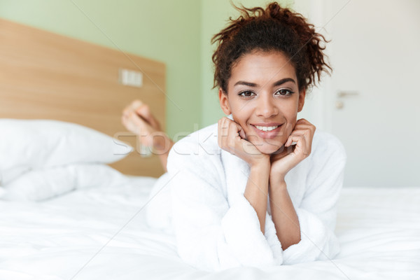 Happy young african woman lies on bed Stock photo © deandrobot