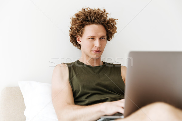 Concentrado hombre mentiras cama casa usando la computadora portátil Foto stock © deandrobot