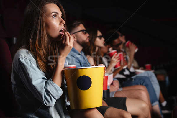 Lady sitting in cinema watch film and eating popcorn. Stock photo © deandrobot