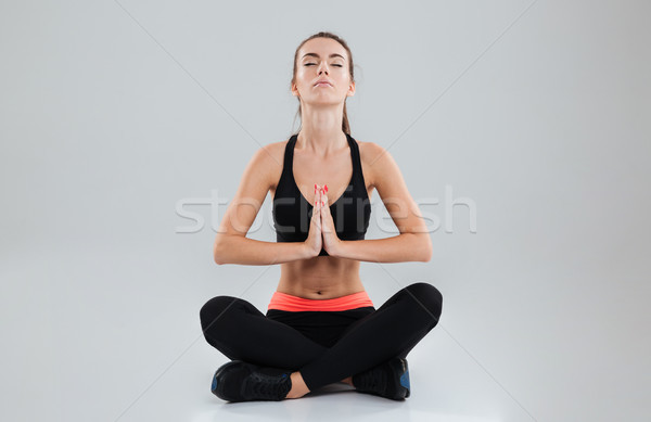 Young calm fitness woman sitting on the floor Stock photo © deandrobot