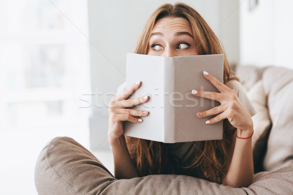 Pretty lady covering face with book. Stock photo © deandrobot