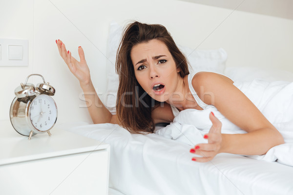 Frustrated confused woman laying in bed Stock photo © deandrobot