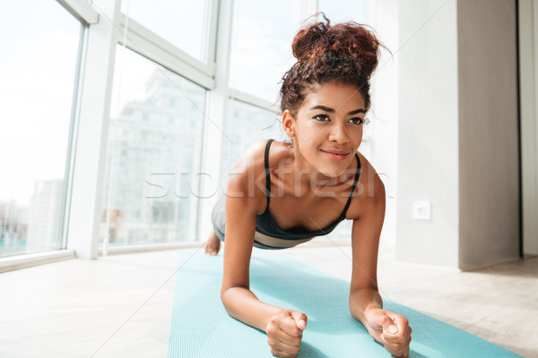 Concentrated sportswoman standing in plank position Stock photo © deandrobot