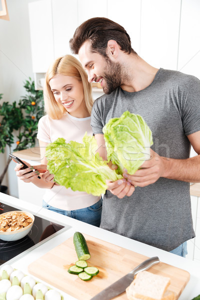 Stock photo: Young loving couple cooking together using mobile phone