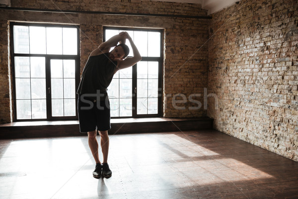 Full length portrait of a young healthy athlete man stretching Stock photo © deandrobot