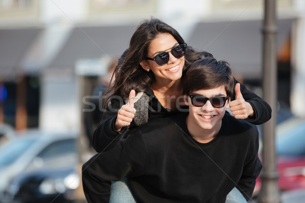 Young woman have fun outdoors with brother showing thumbs up. Stock photo © deandrobot