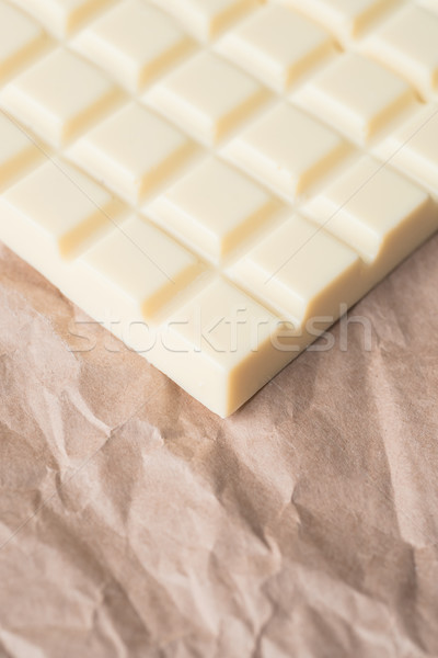 Close-up of white chocolate bar over paper Stock photo © deandrobot