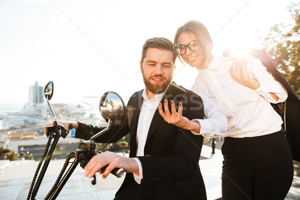 Pleased business woman standing near bearded man in suit Stock photo © deandrobot