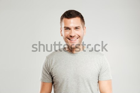 Happy young man dressed in grey t-shirt isolated Stock photo © deandrobot