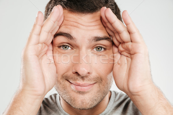 Smiling man covering face with hands. Looking camera. Stock photo © deandrobot