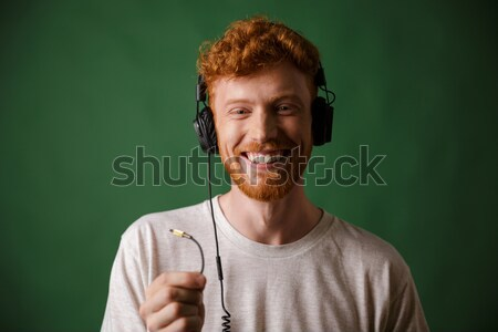 Close-up shot of smiling readhead man, combing his beard with pi Stock photo © deandrobot