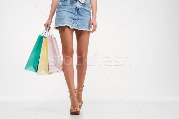 Close up of female legs in skirt holding shopping bags Stock photo © deandrobot