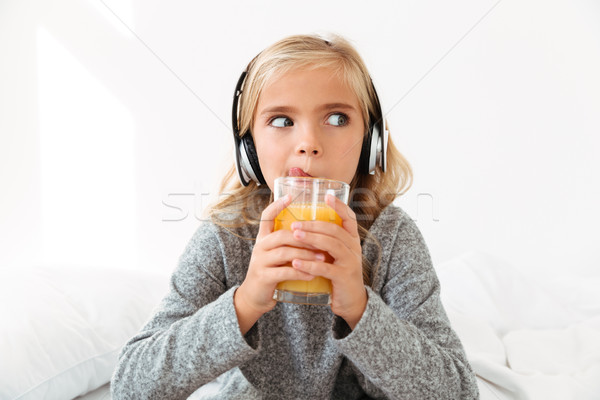 Close-up photo of pretty little girl in headphones licking while Stock photo © deandrobot