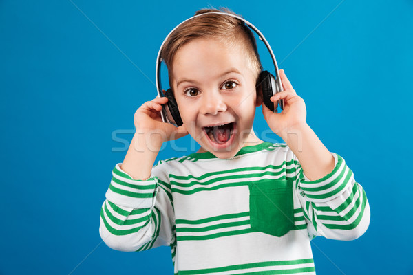 So happy young boy listening music by headphone Stock photo © deandrobot